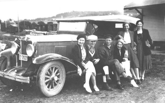 Old black and white photo with people standing next to an old Chevrolet